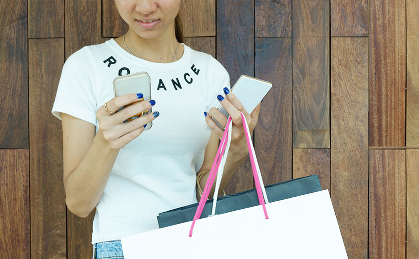 Girl holding a mobile phone and shopping bags